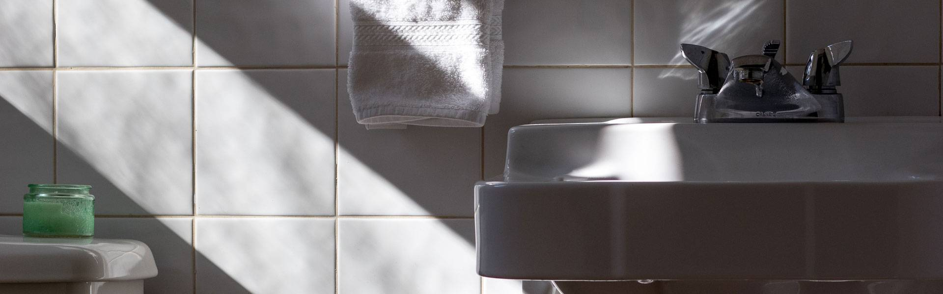 close up of white porcelain tiles behind a white cotton towl and bathroom sink