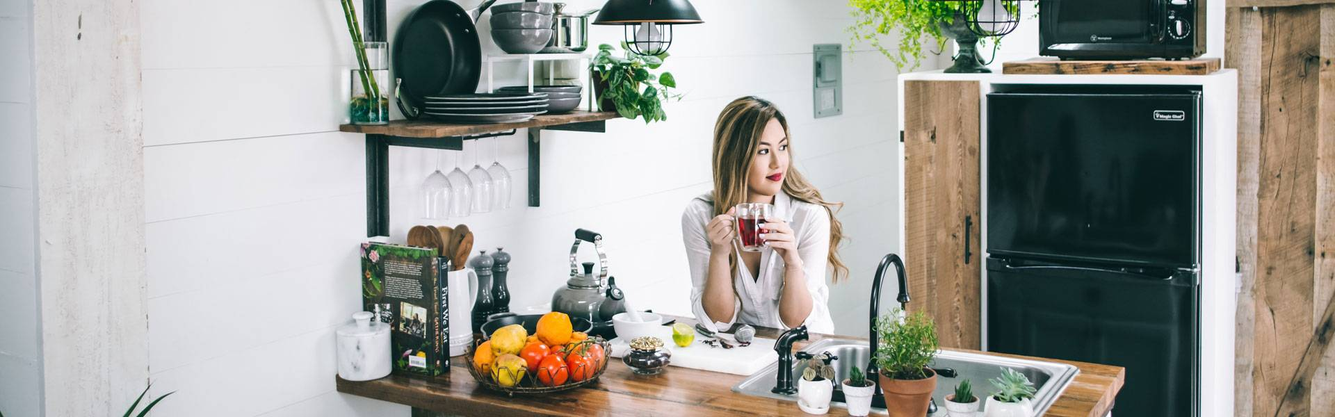 woman drinking tea and leaning on top of rustic wooden kitchen worktop surface