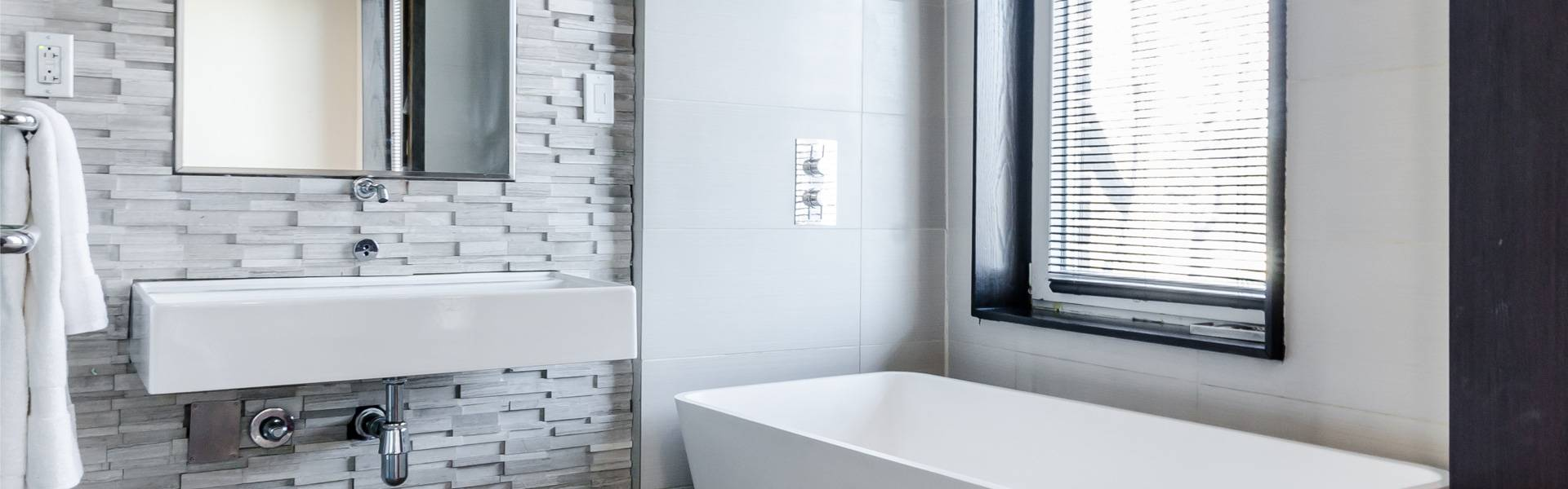 thin grey slate tiles on wall of a large mirror and bathroom sink